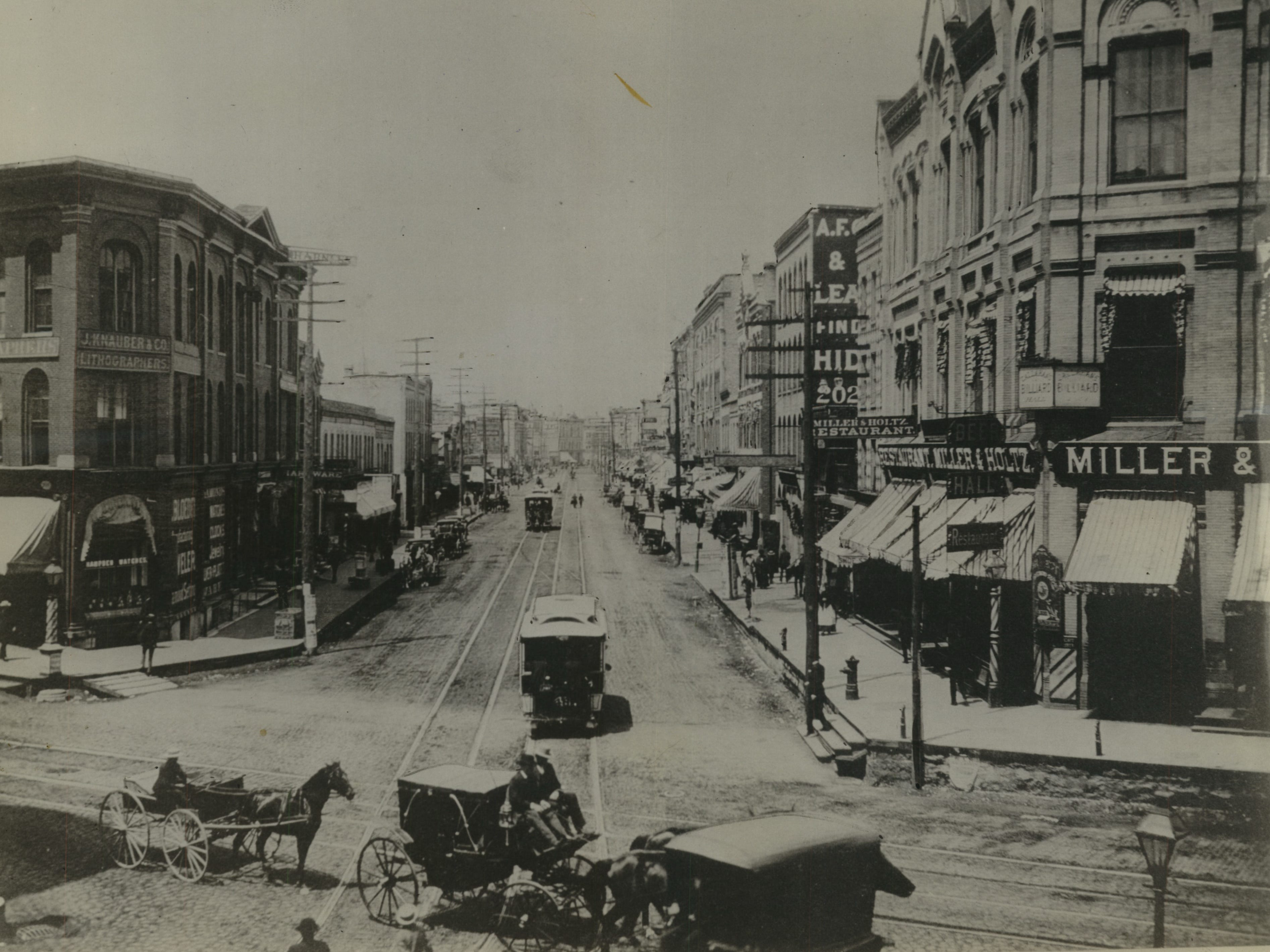 There isn't an automobile in sight in this old picture of the intersection of West Waters street (now North Plankinton avenue) and Grand avenue (now West Wisconsin avenue). The camera was pointed north when the picture was taken. Notice the horse-drawn street cars and how high the sidewalk at the right is above the street. A man may be seen walking down three steps to get to the street. He may have just come out of Miller & Holtz's restaurant and beer hall. Milwaukee - Streets - Plankington avenue - Historic. Looking up West Water street from Grand avenue. View Down North Plankinton Avenue from West Wisconsin Avenue