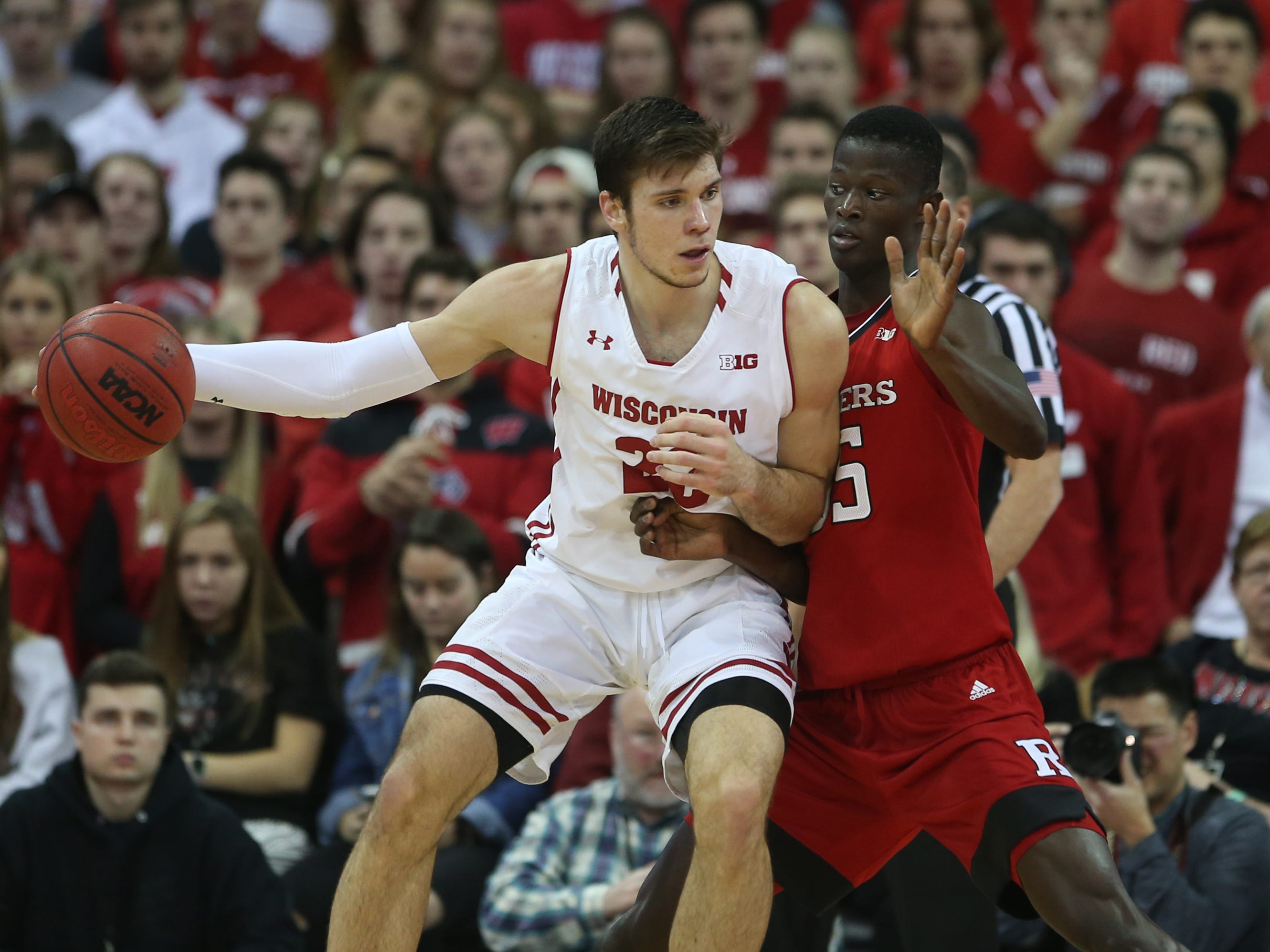 Badgers forward Ethan Happ tries to back down Issa Thiam of Rutgers in the post in first half Monday night.