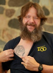 Craig Pavlik, the aquatic and reptile keeper, shows the lion tattoo on his chest he got when he used to work with the big cats.