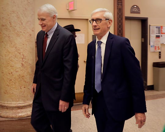 Mayor Tom Barrett (left) walks through Milwaukee City Hall Tuesday morning with Gov.-elect Tony Evers.