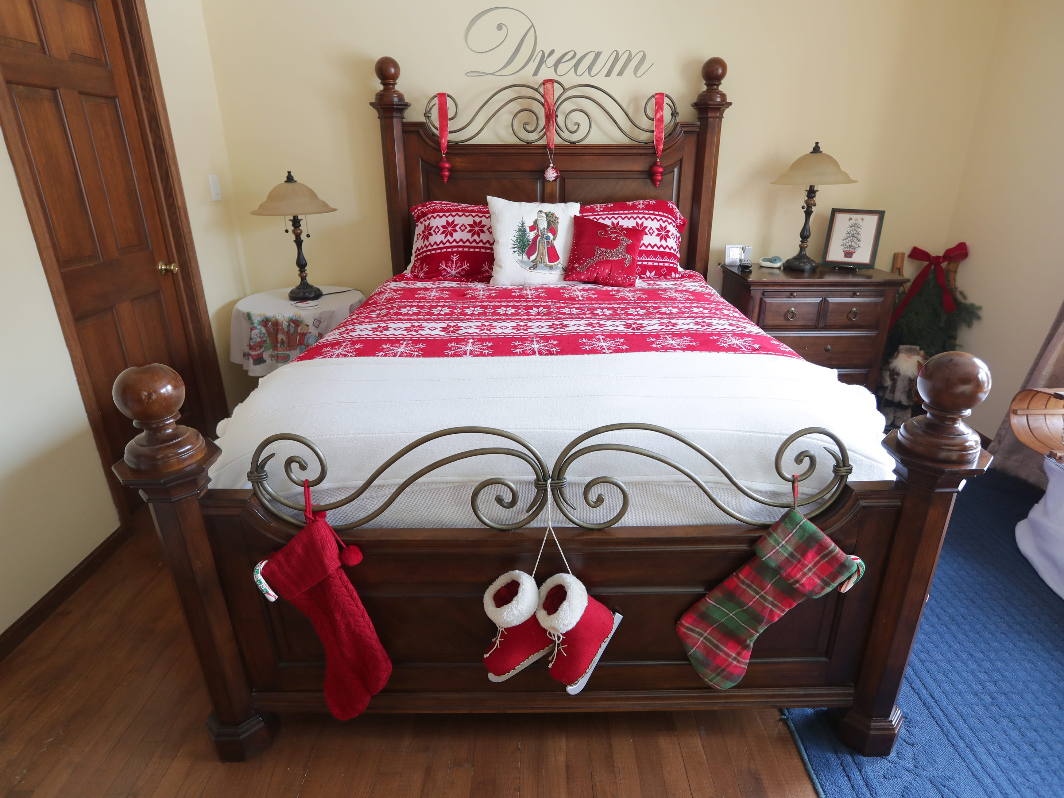 A bed with Christmas blankets, pillows and other decorations is featured in the guest bedroom on the first floor.