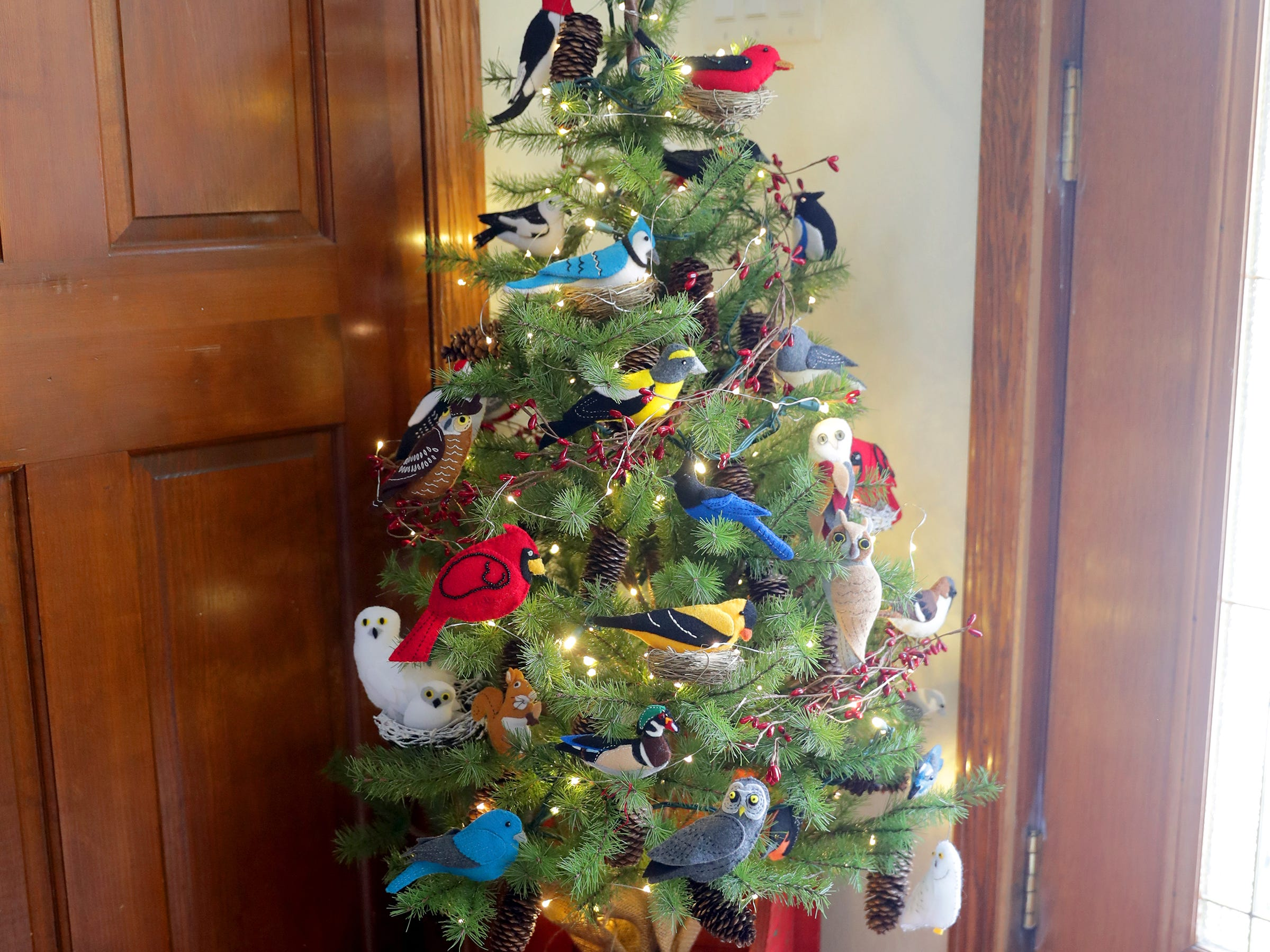 A small tree near the entryway is decorated with homemade felt birds created by Renee Sirny.