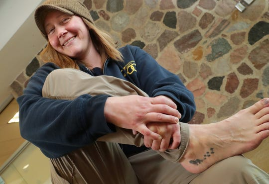 Katie Kuhn, the Big Cat Country supervisor, shows her foot tattoo of the first male lion she ever worked with and the paw prints of his mate.