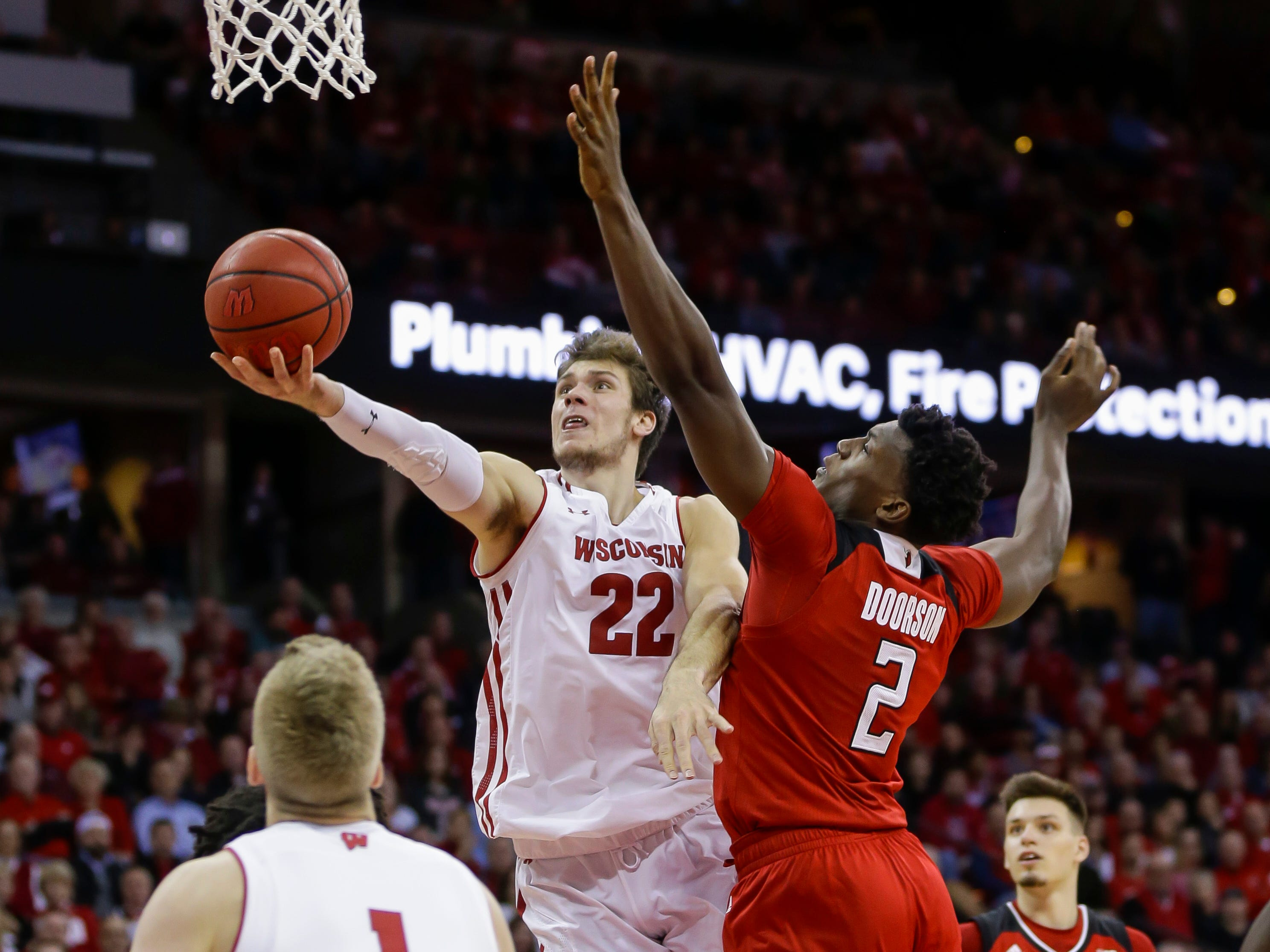 Wisconsin's Ethan Happ puts up a underhanded shot near the hoop against Rutgers' Shaquille Doorson  during the second half on Monday night at the Kohl Center.