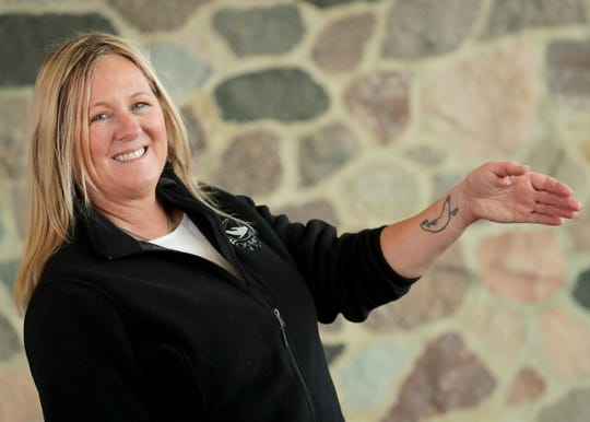 Shelley Ballmann, president of Oceans of Fun, shows her sea lion tattoo.
