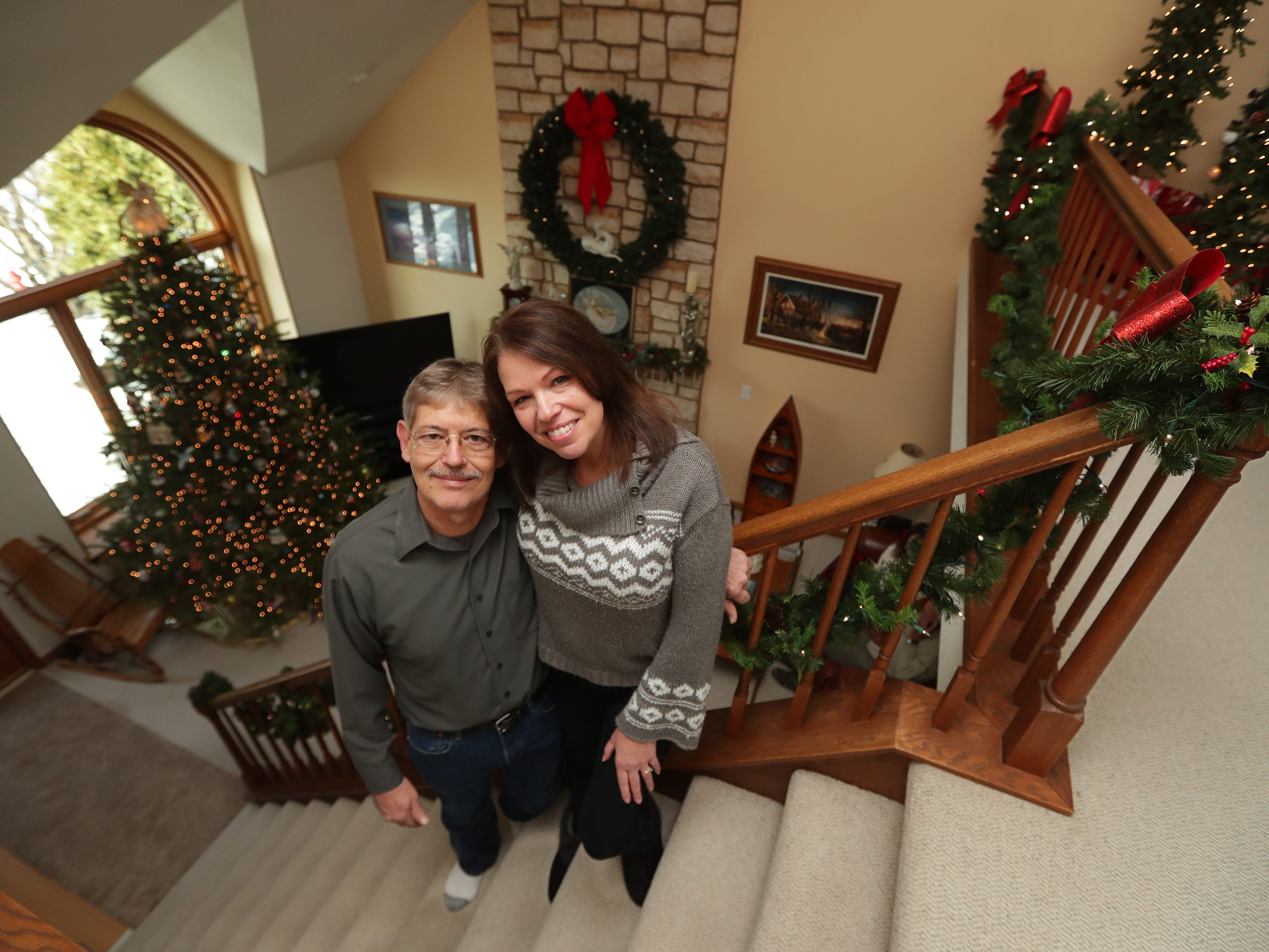 Renee and Lee Sirny stand on the staircase leading to the second floor of their Muskego home, which is elaborately decked out for the holidays.