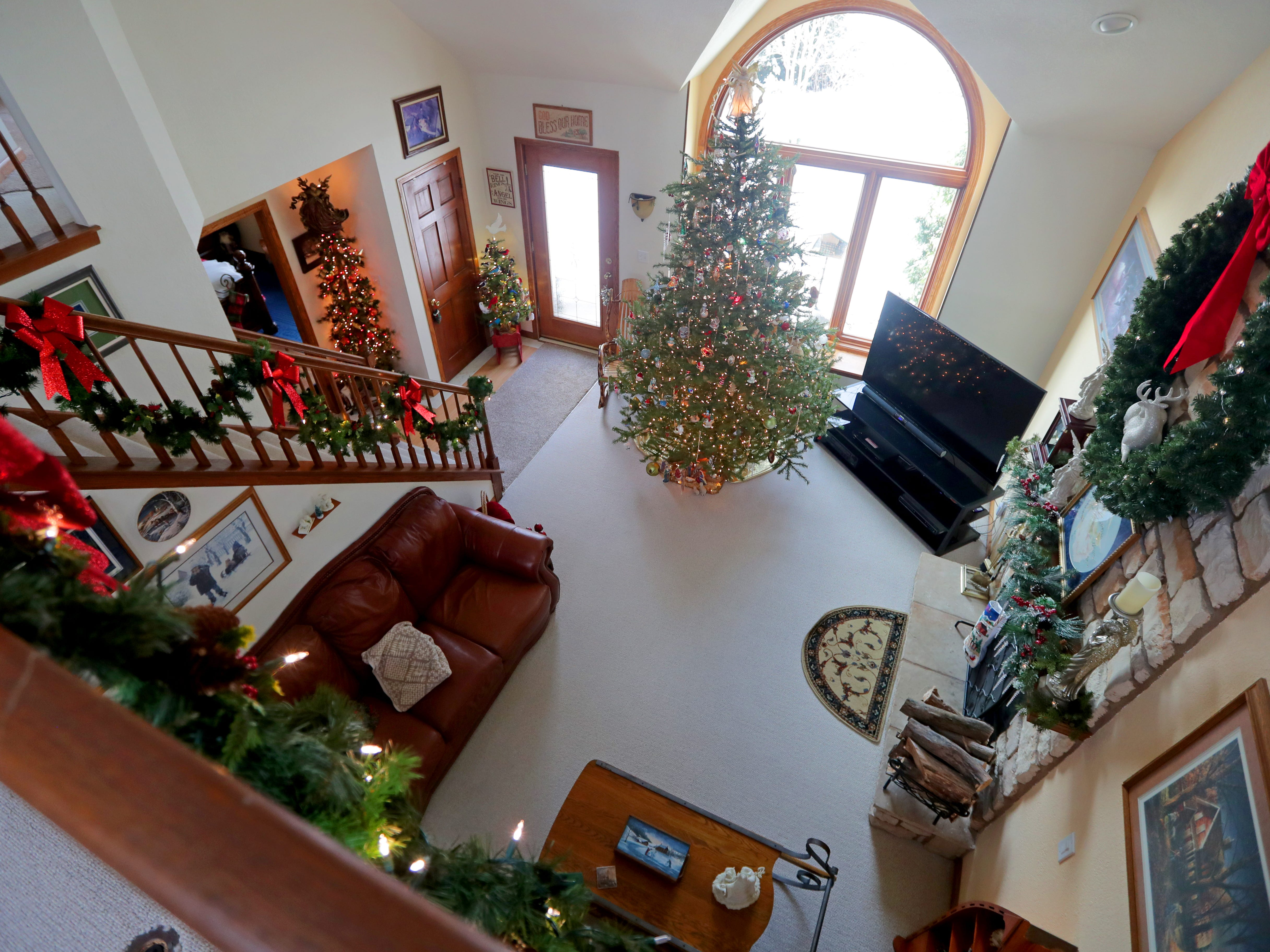 The view from the balcony shows a festively decorated living room below.