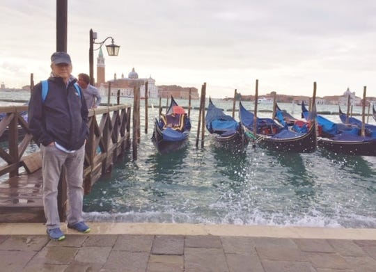 Rob Newcomer standing at the Grand Canal on as water laps and eventually floods St. Mark's Square with several inches of water.