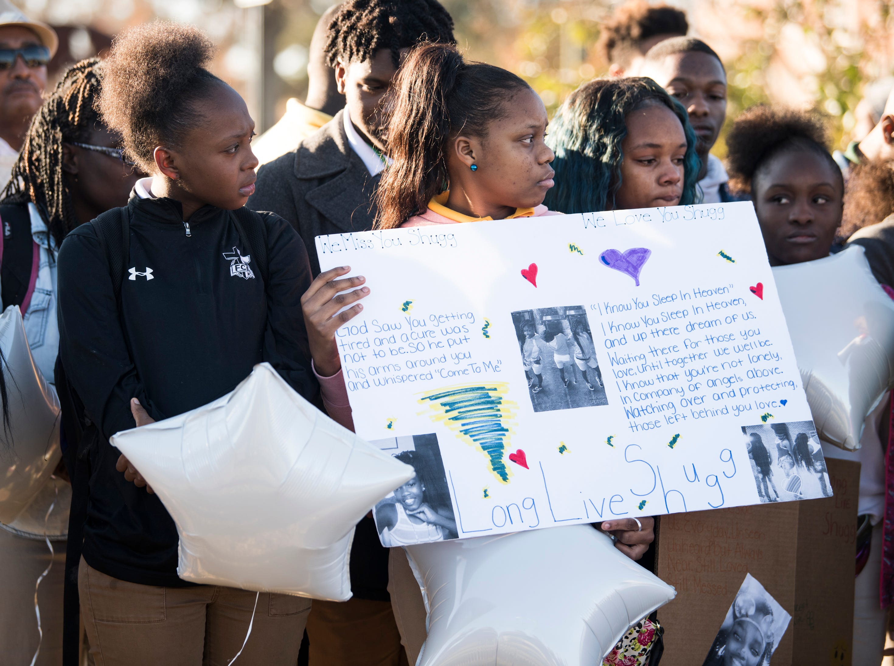Friends remember Keiauna Williams during a vigil across from Carver High School in Montgomery, Ala., on Tuesday, Dec. 4, 2018. Williams was died after being hit by a car Saturday night.