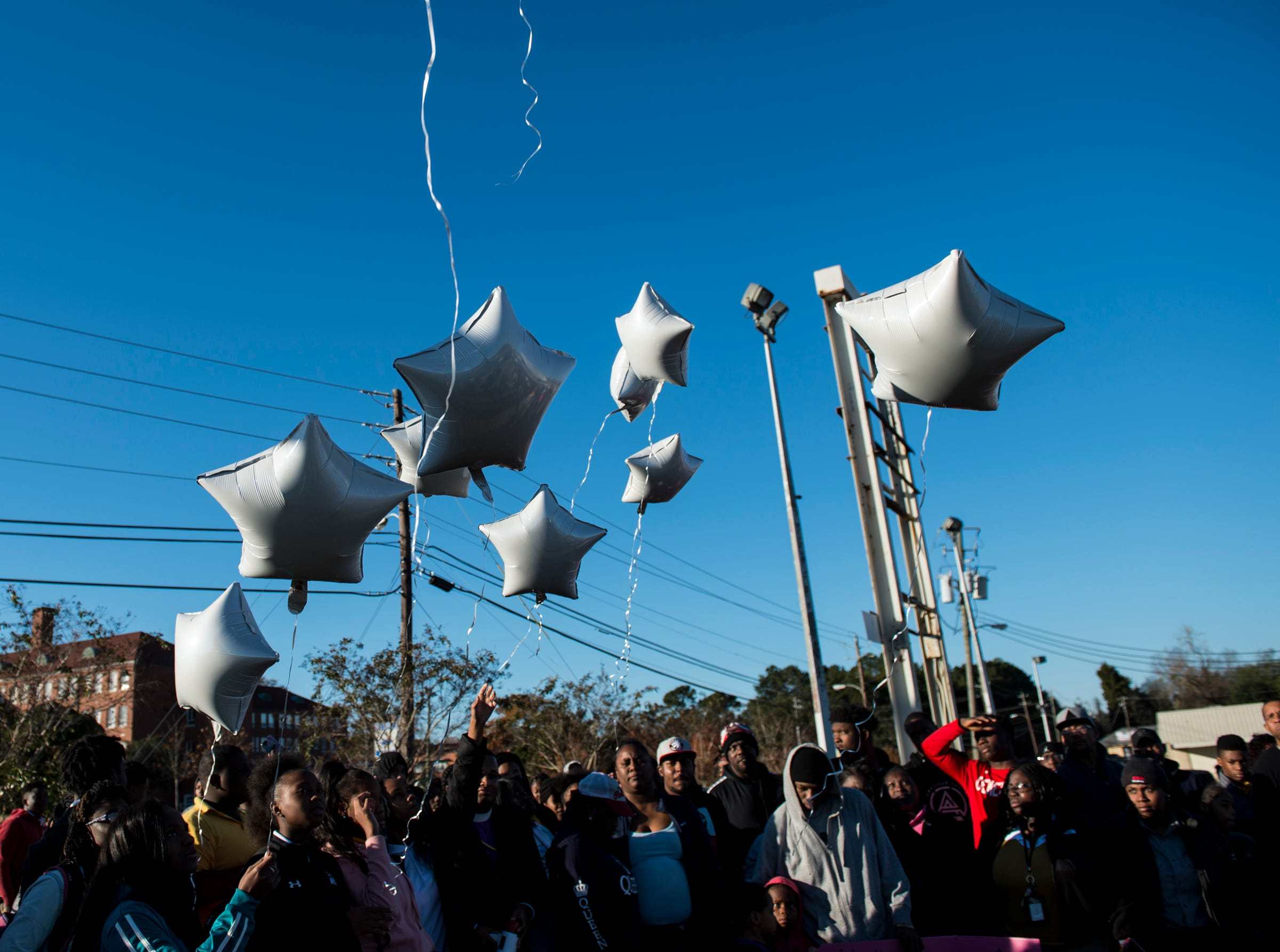 Ballons are released during a vigil for Keiauna Williams across from Carver High School in Montgomery, Ala., on Tuesday, Dec. 4, 2018. Williams was died after being hit by a car Saturday night.