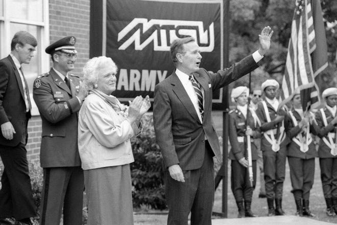 In this Aug. 29, 1988, file photo, Vice President George H.W. Bush waves as his wife, Barbara Bush, looks on after his remarks to military science cadets at Middle Tennessee State University. Lt. Col. Cal Calloway, chair of the Department of Military Science, and a Secret Service agent are shown in the background. The Bushes visited MTSU as part of a fundraising trip to Nashville during the 1988 presidential campaign.