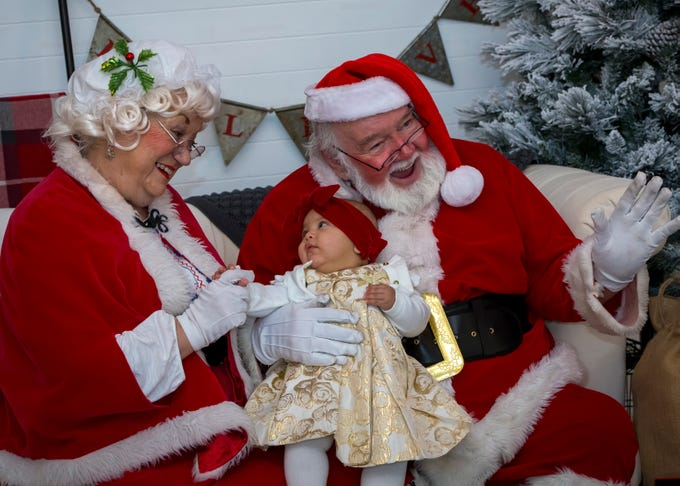 While Santa smiles for the camera Chole Grace Curtis and Mrs. Santa share a moment during pictures with Santa at Fountains of Gateway.