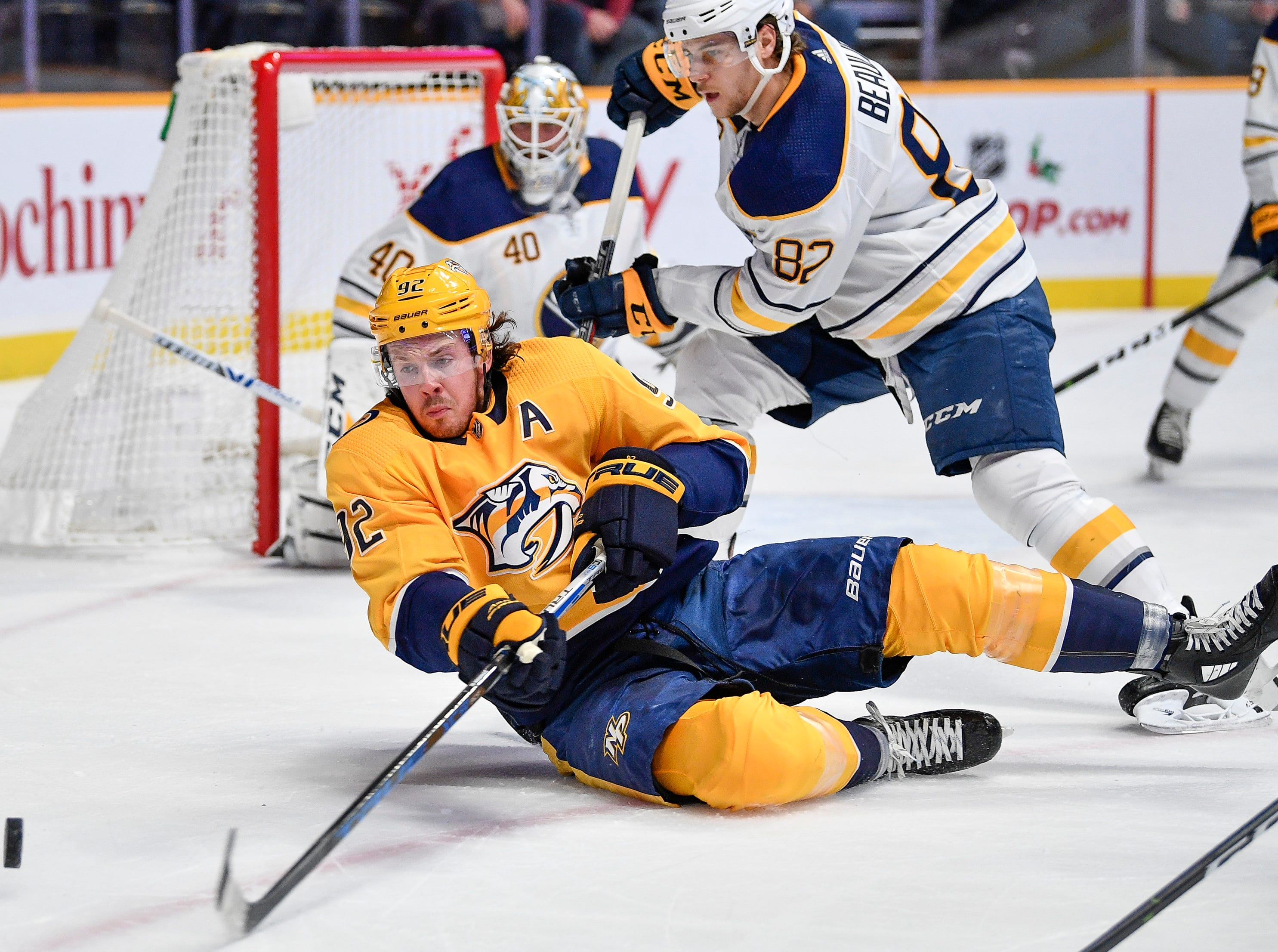Nashville Predators center Ryan Johansen (92) dives for the puck with Buffalo Sabres defenseman Nathan Beaulieu (82) during the first period at Bridgestone Arena in Nashville, Tenn., Monday, Dec. 3, 2018.