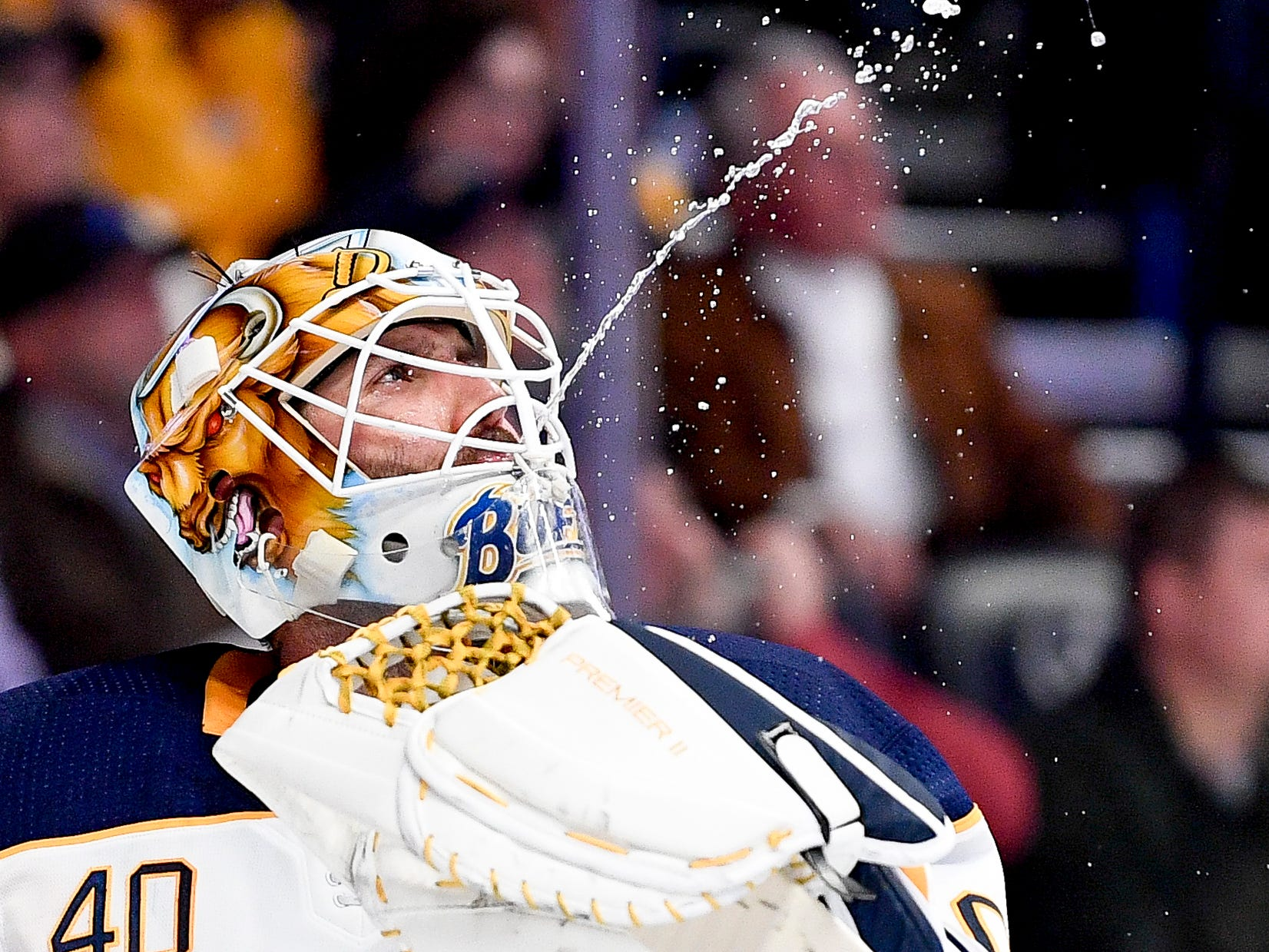 Buffalo Sabres goaltender Carter Hutton (40) spits out water while waiting for gameplay to resume against the Nashville Predators during the first period at Bridgestone Arena in Nashville, Tenn., Monday, Dec. 3, 2018.