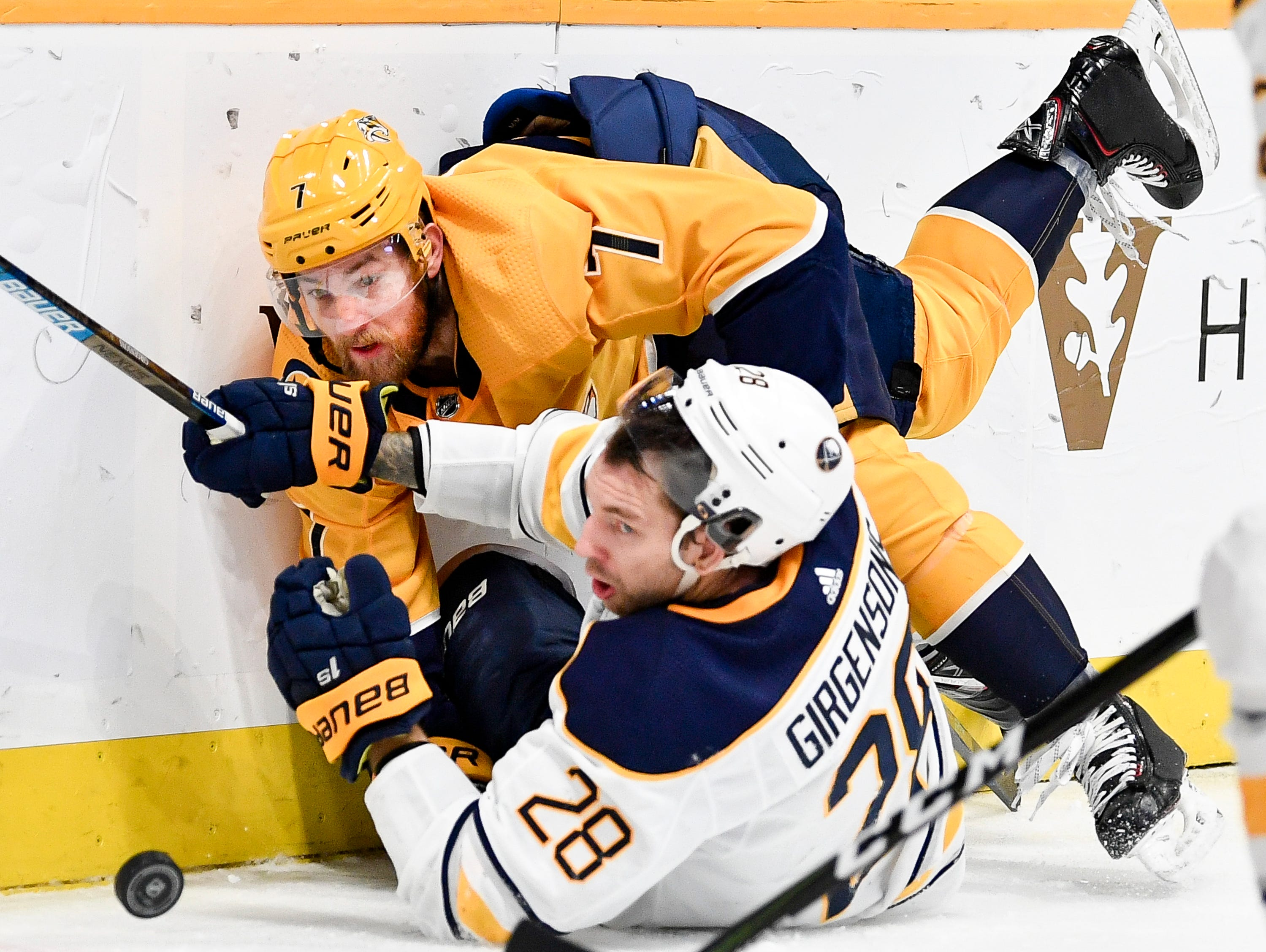 Nashville Predators defenseman Yannick Weber (7) collides with Buffalo Sabres center Zemgus Girgensons (28) during the second period at Bridgestone Arena in Nashville, Tenn., Monday, Dec. 3, 2018.