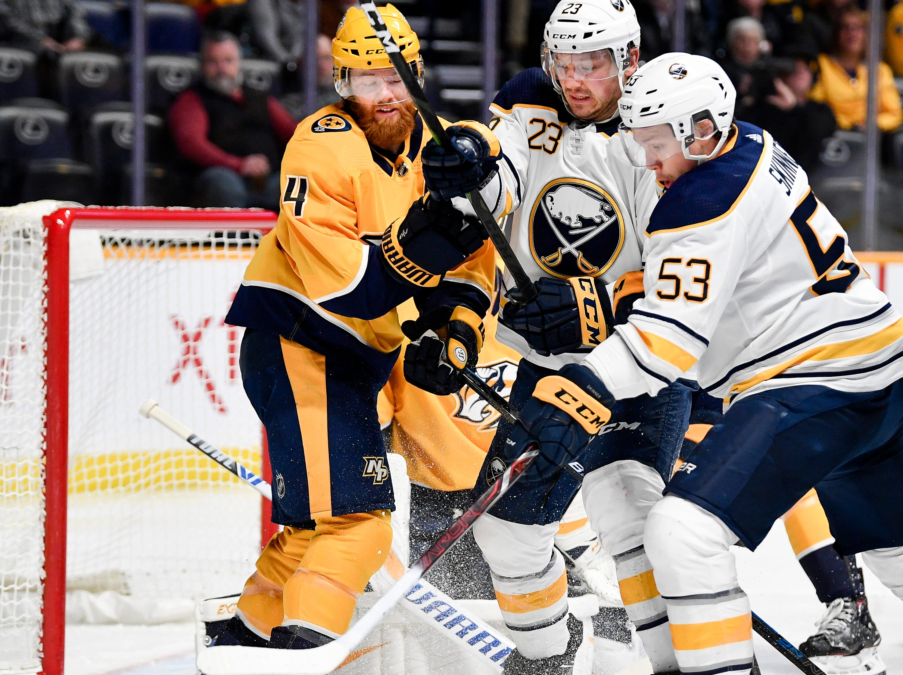 Nashville Predators defenseman Ryan Ellis (4) defends against Buffalo Sabres center Sam Reinhart (23) and left wing Jeff Skinner (53) during the second period at Bridgestone Arena in Nashville, Tenn., Monday, Dec. 3, 2018.