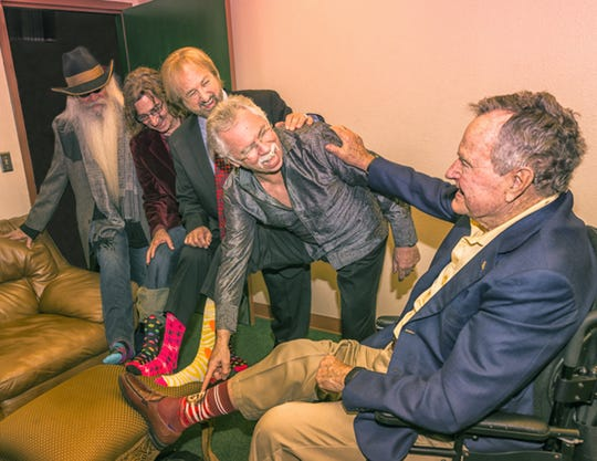 The Oak Ridge Boys compare colorful socks with former President George H. W. Bush.
