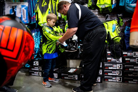 Scott Gabster, general manager of Florida Motorsports, helps Cole Williams try on riding gloves during his Make-A-Wish celebration on Monday, Dec. 3, 2018, at Florida Motorsports in North Naples. Gabster's son was a Make-A-Wish recipient six years ago, and he was happy to help make Cole's wish for a dirt bike come true.