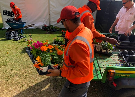 Workers move flowers to decorate the event spaces prior to the games at Tiburón Golf Club at The Ritz-Carlton Golf Resort in North Naples on Tuesday, Dec. 4, 2018