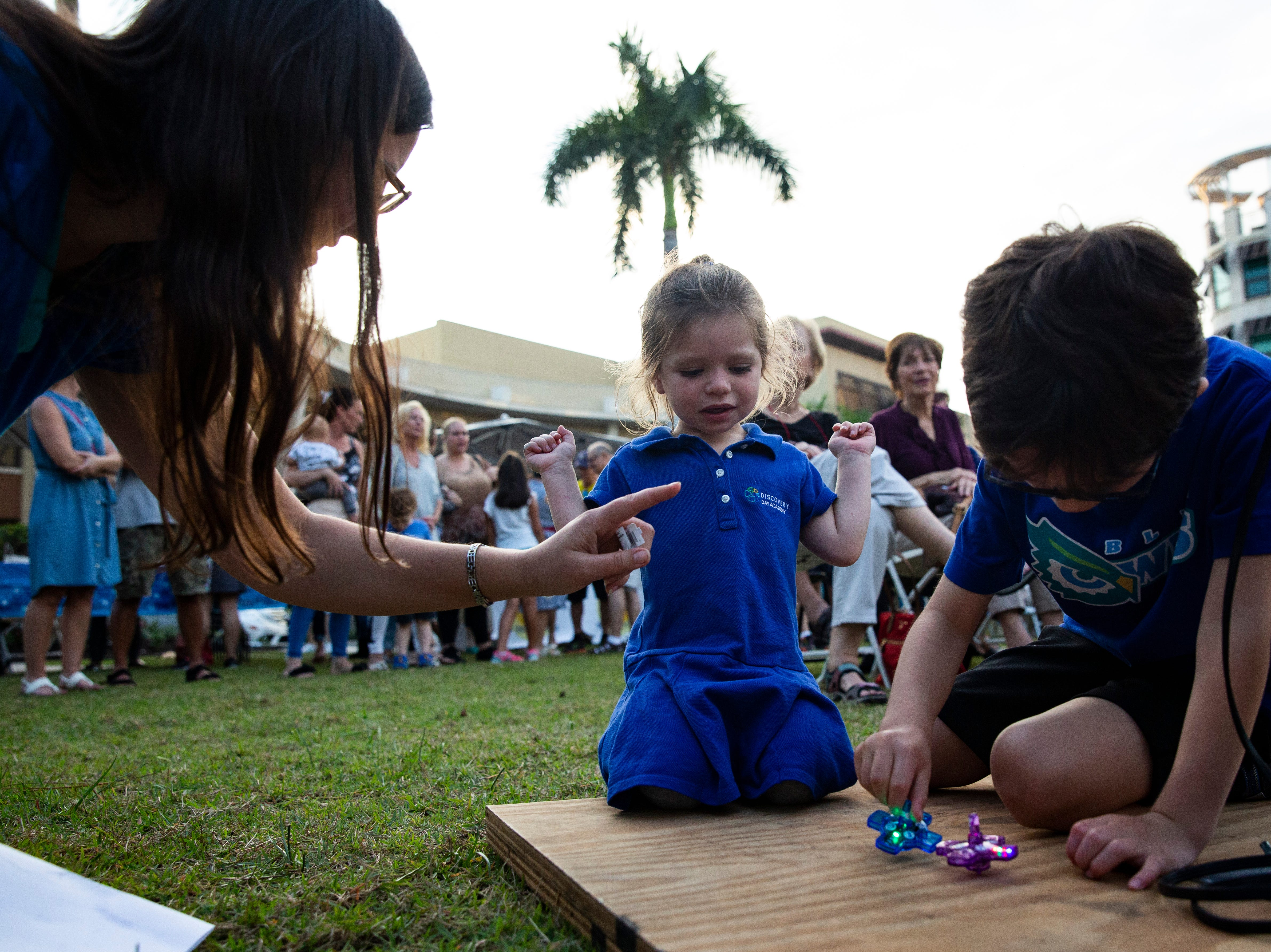 Sarah Cohen, 3 and brother, Eli Cohen, 6, play with electronic dreidel during the  20th annual Hanukkah Celebration at the Mercato Lawn on Monday, Dec. 3, 2018, by the Jewish Federation.