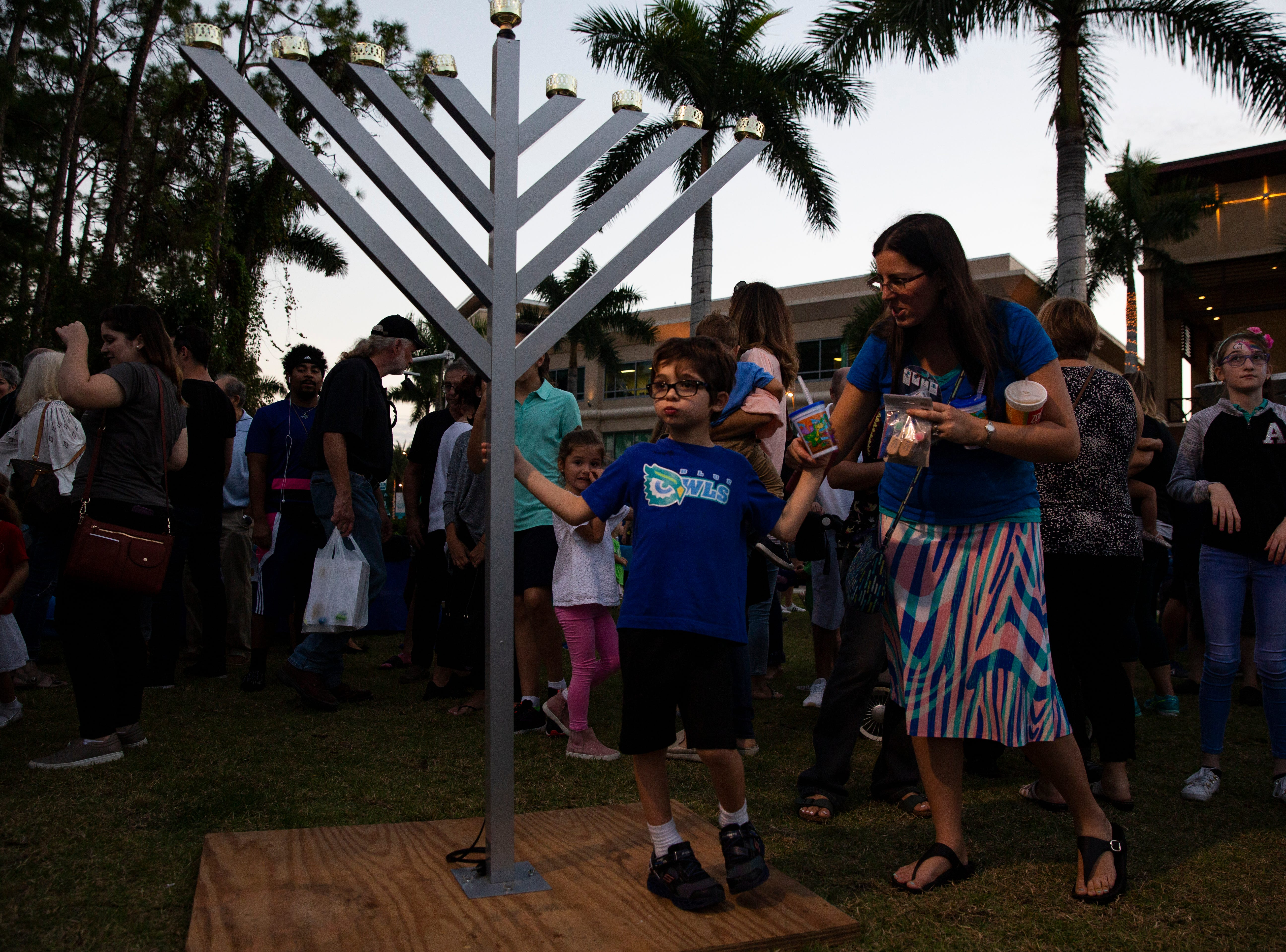 Eli Cohen, 6, stands by the menorah listening to the band play music during the  20th annual Hanukkah Celebration at the Mercato Lawn on Monday, Dec. 3, 2018, by the Jewish Federation.