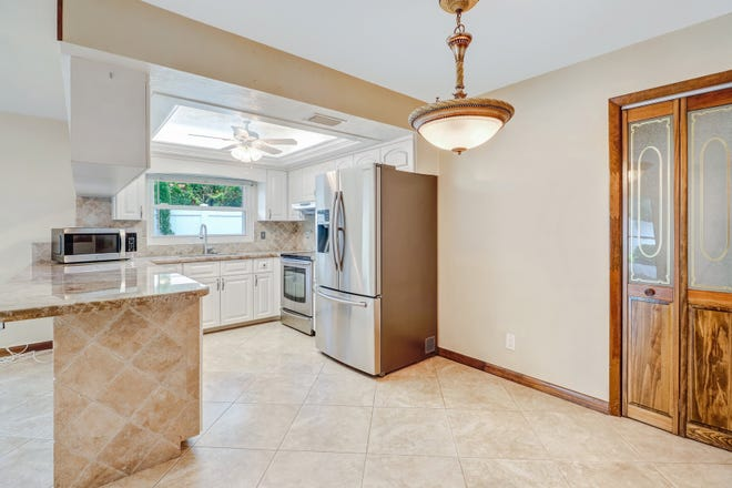 After: A Naples kitchen staged by Naples Realtor Karly Carballea. She removed the curtains and de-cluttered the counter tops to make the room more visually appealing.
