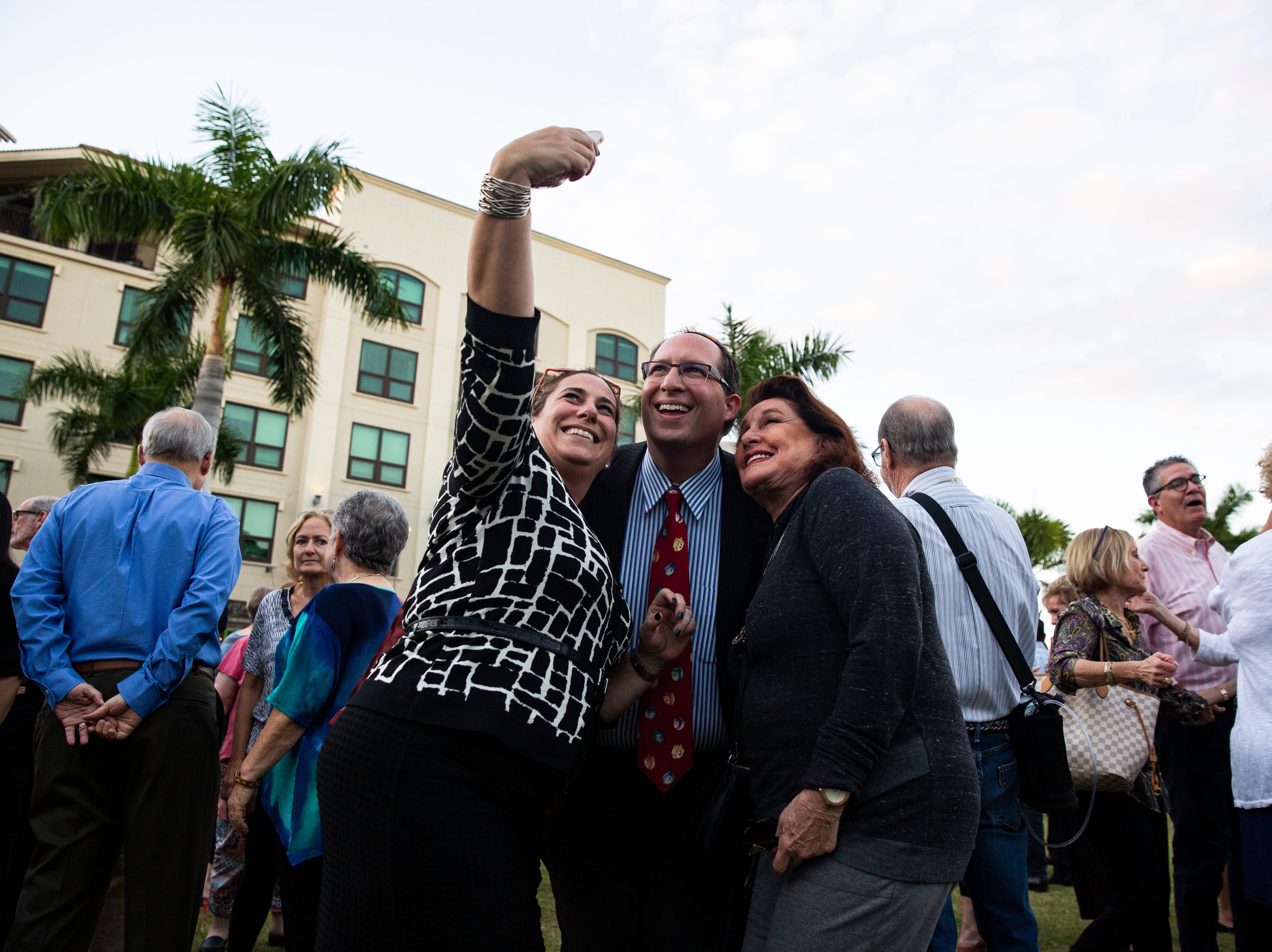 Rabbi Adam Miller (center) of Temple Shalom takes a selfie with, Jennifer Siegal-Miller (left) and Marcy Aizenshtat at the 20th Hanukkah celebration put up by the Jewish Federation at the Mercato Lawn on Monday, Dec. 3, 2018.