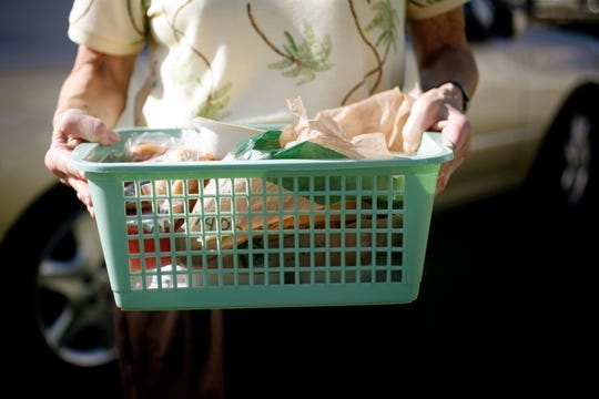 A Meals on Wheels volunteer carries a basket of food into a Southwest Florida home in 2013.