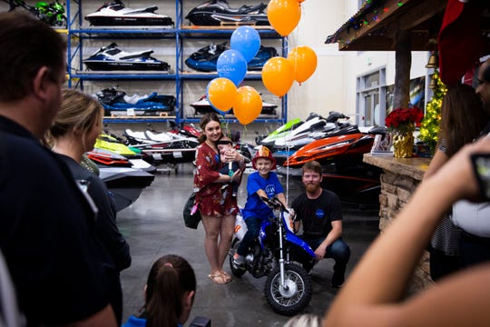 Cole Williams poses for a photo with his dad, Gary Williams, his stepmom, Amanda Williams, and his baby sister Emma Williams while sitting on his new custom dirt bike from the Make-A-Wish foundation on Monday, Dec. 3, 2018, at Florida Motorsports in Naples.