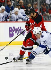 Tampa Bay Lightning center Anthony Cirelli (71) and New Jersey Devils left wing Taylor Hall (9) battle for the puck during first period at Prudential Center.