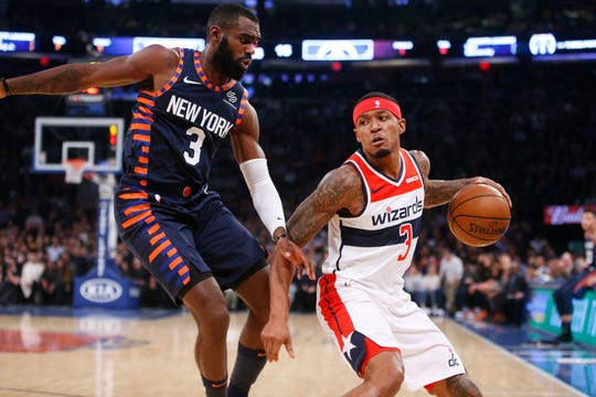 Washington Wizards' Bradley Beal, right, drives against New York Knicks' Tim Hardaway Jr. during the first quarter of an NBA basketball game Monday, Dec. 3, 2018, in New York.