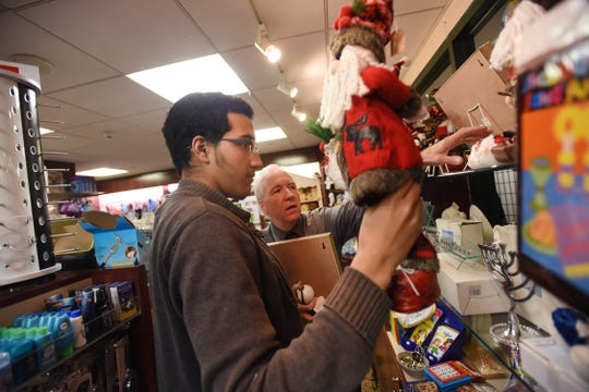 Project SEARCH intern Kenneth Machorro (age 20) of Englewood, is helped by gift shop manager, Patrick Finnegan, as he sorts out items at the gift shop located at the main lobby of Holy Name Medical Center in Teaneck on 12/04/18.