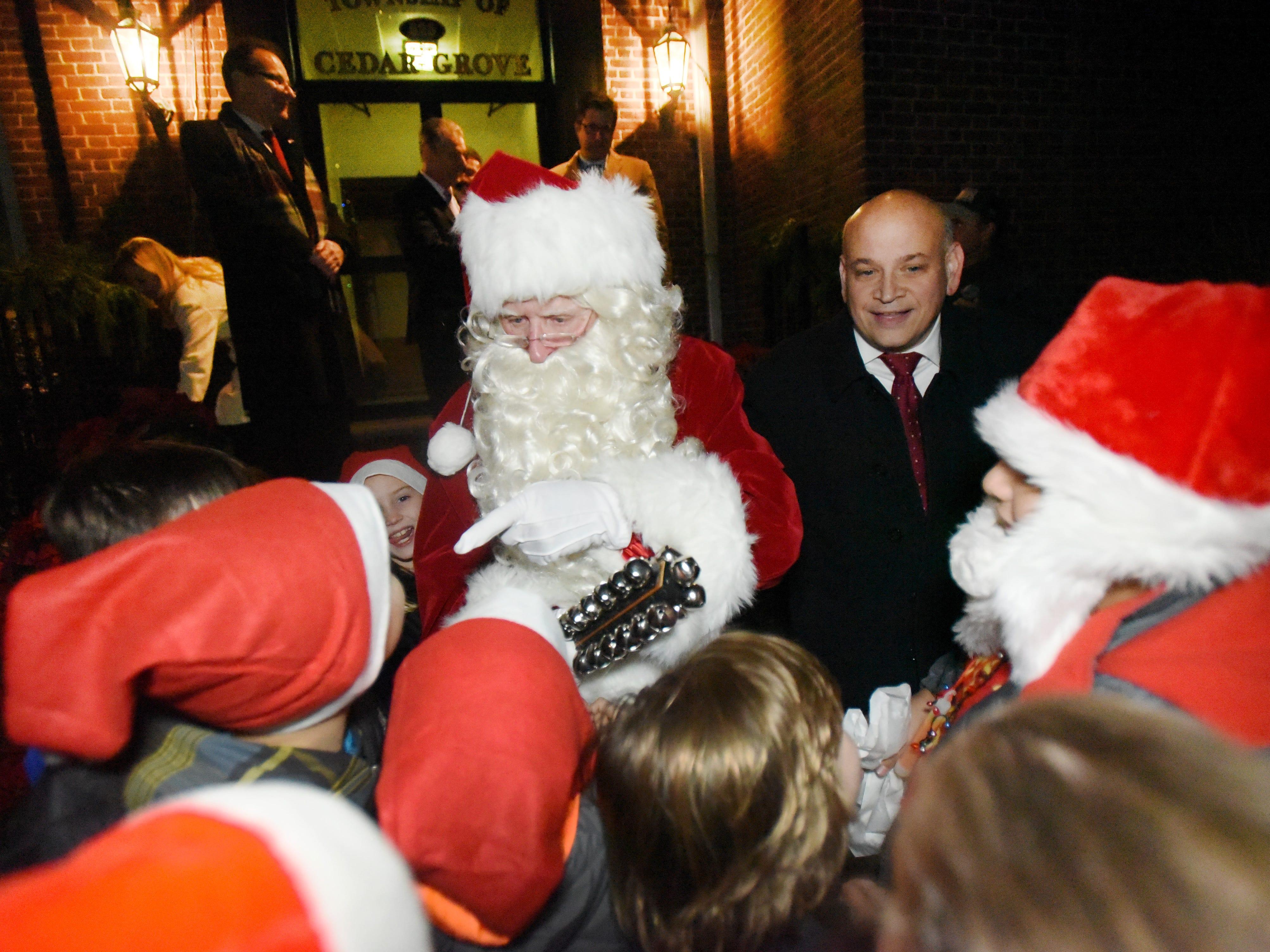 As Mayor Joseph Cicala (R) looks on, Santa (Kris Kringle) greets children following the Christmas Tree Lighting ceremony at Cedar Grove Town Hall on 12/03/18.