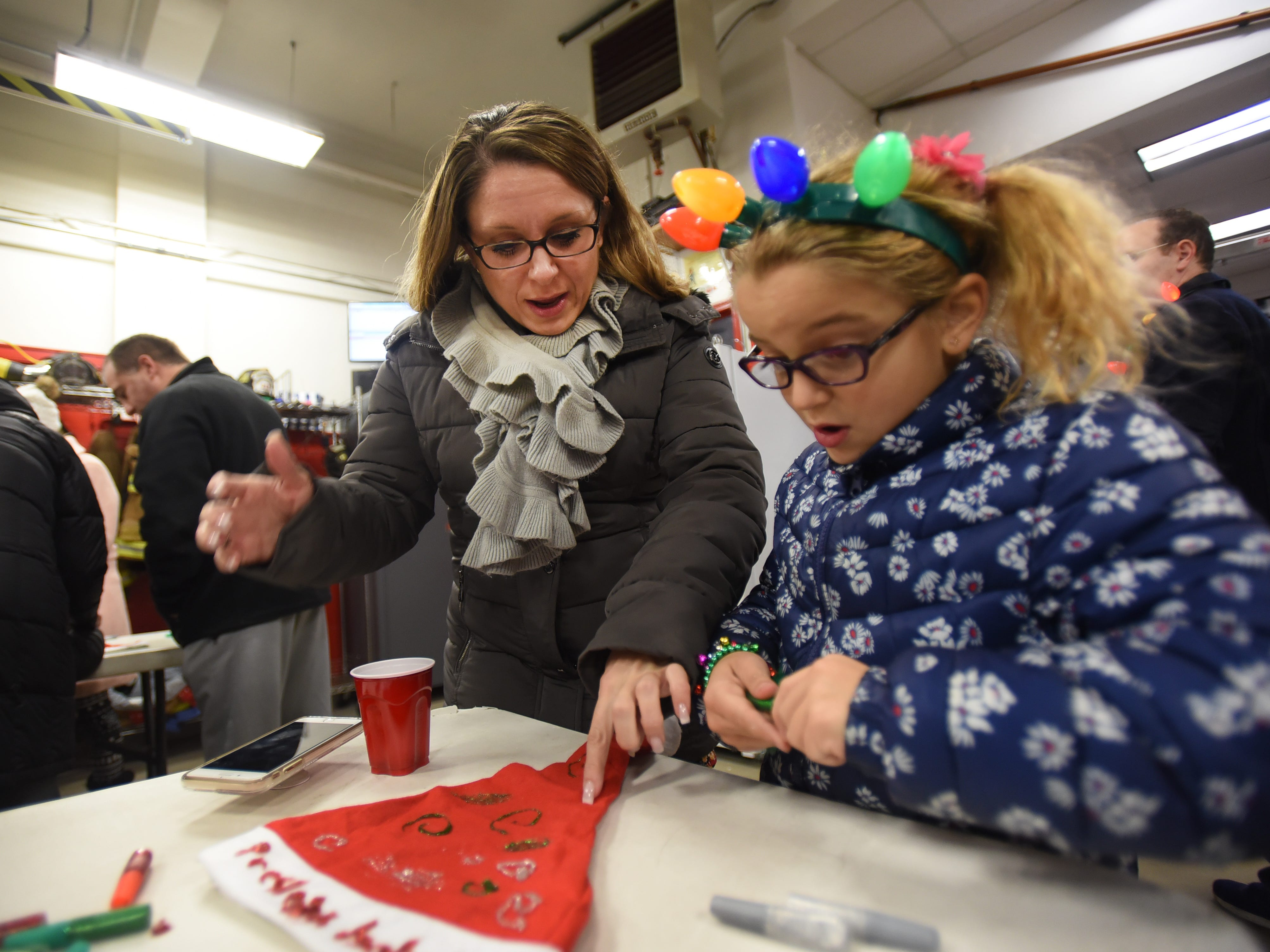 Presleigh Coronado (age 7) decorates her Christmas cap helped by her mother Alicia prior to the Christmas Tree Lighting ceremony at Cedar Grove Town Hall on 12/03/18.