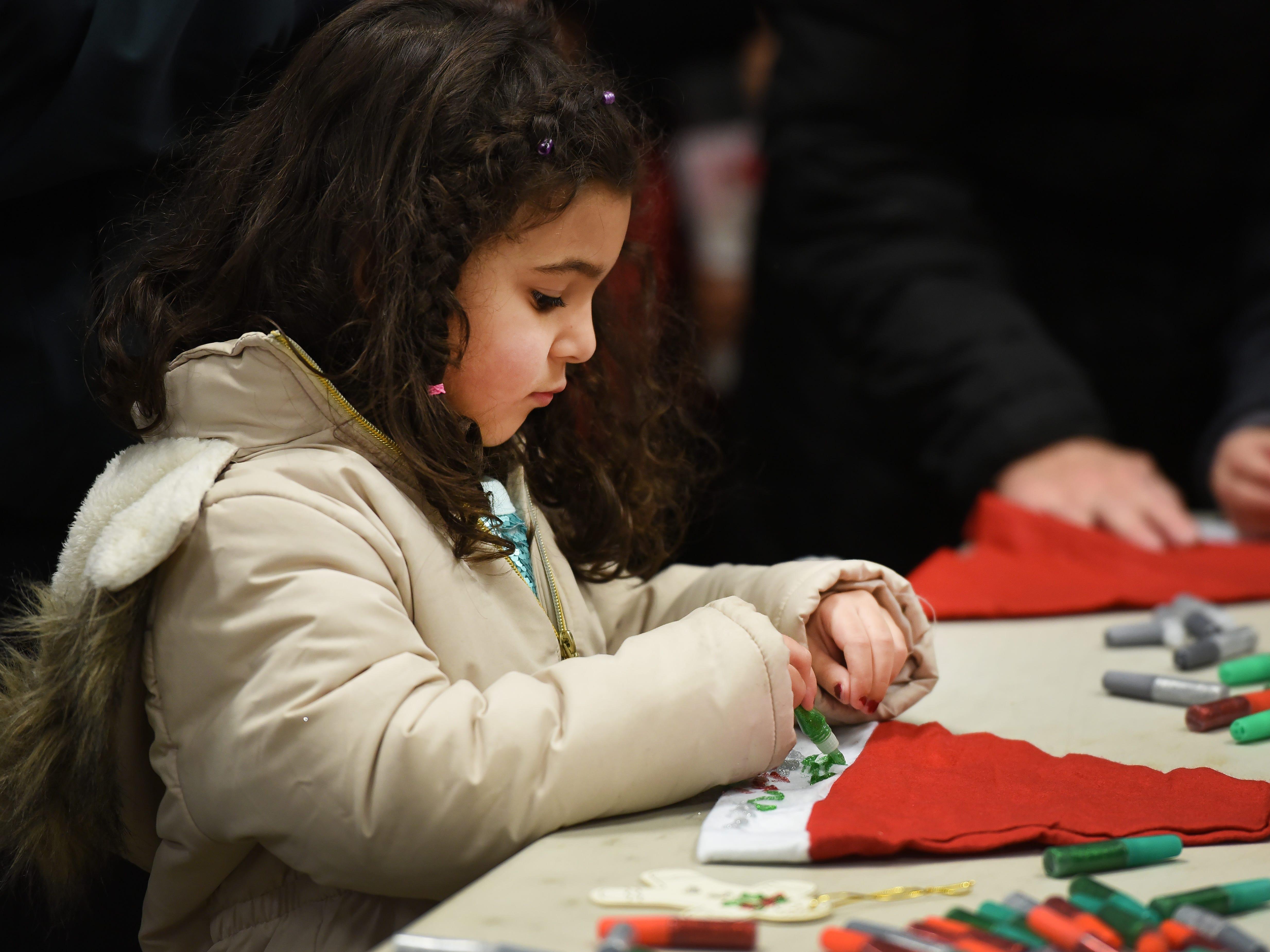 Natalia Dressler (age 5) decorates a Christmas cap prior to the Christmas Tree Lighting ceremony at Cedar Grove Town Hall on 12/03/18.