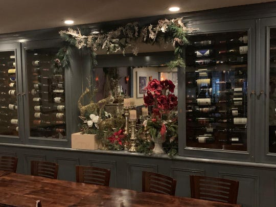 Biagio has candles, garland and poinsettias near its wine selection.