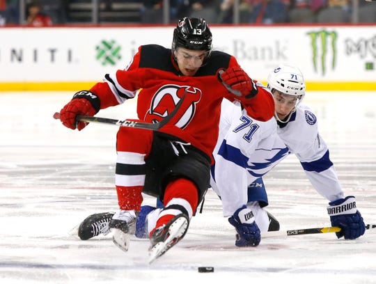 New Jersey Devils center Nico Hischier (13) and Tampa Bay Lightning center Anthony Cirelli (71) battle for the puck during first period at Prudential Center.