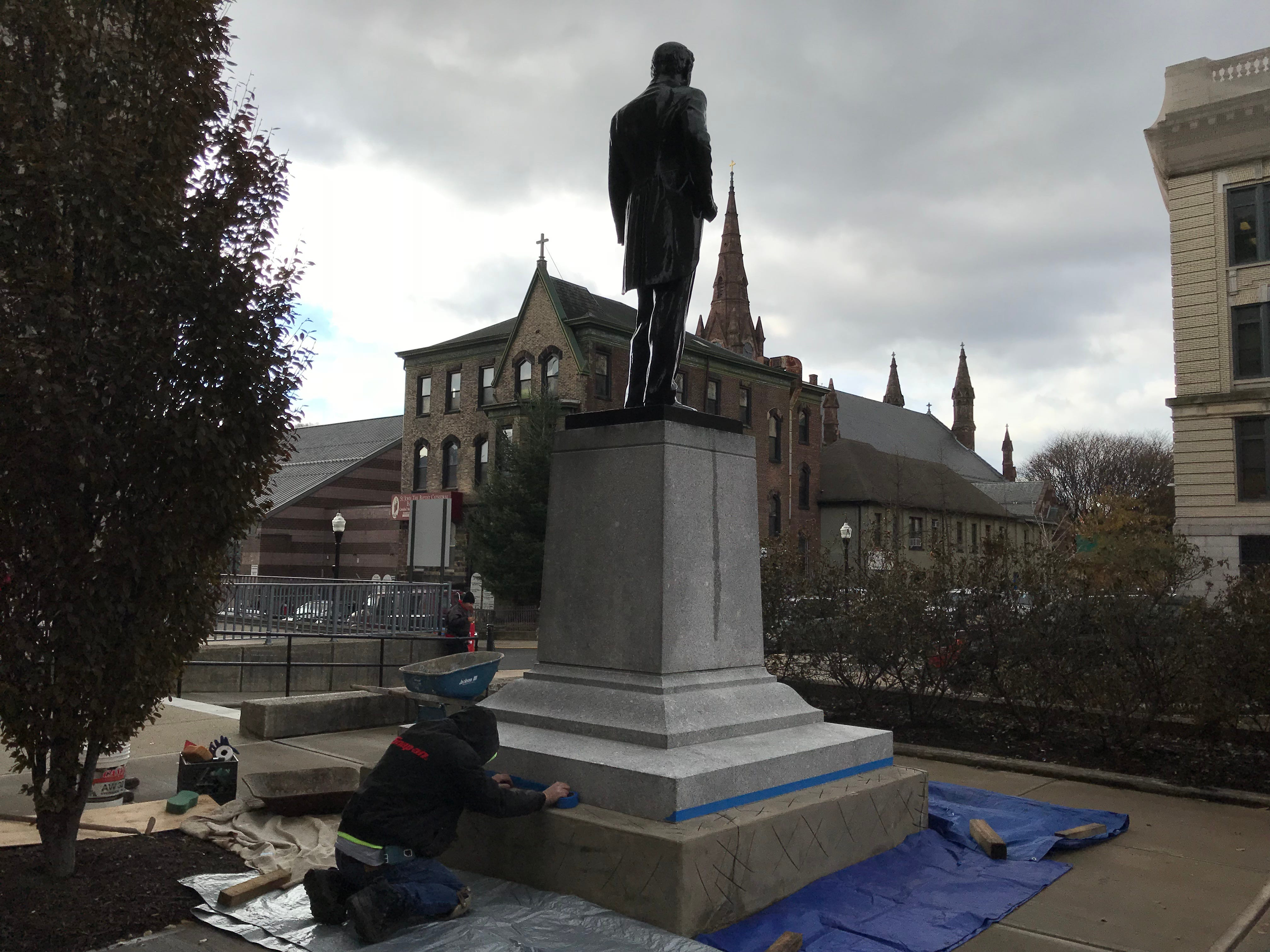 A stone mason restoring the granite base of the William Hughes monument in front of the Passaic County Courthouse in Paterson.