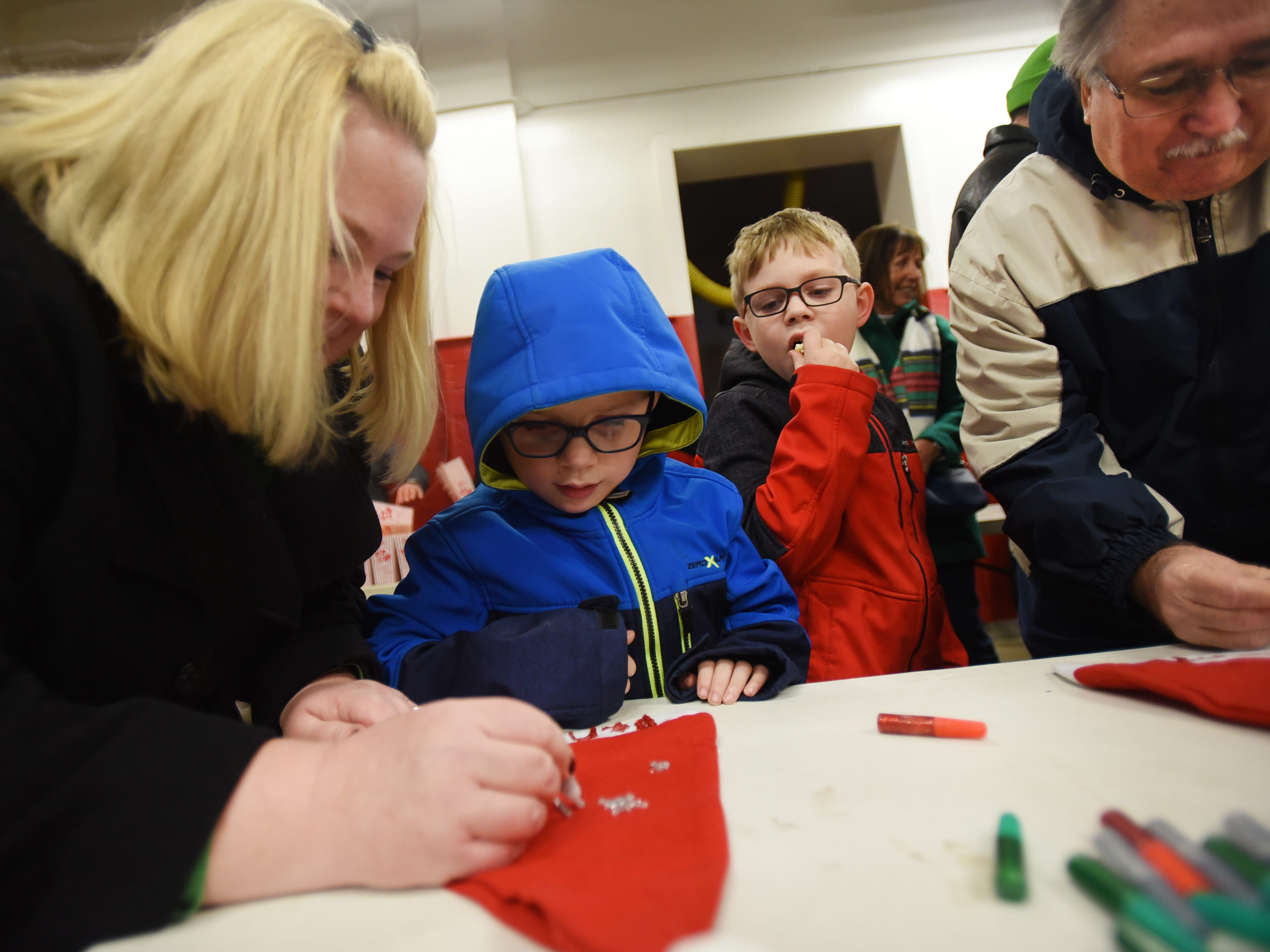 Seven year old twins Ben and Anthony Palamara work on decorating Christmas caps helped by their mother Cathy and their Grandfather Ken Geiselmann (R) prior to the Christmas Tree Lighting ceremony at Cedar Grove Town Hall on 12/03/18.