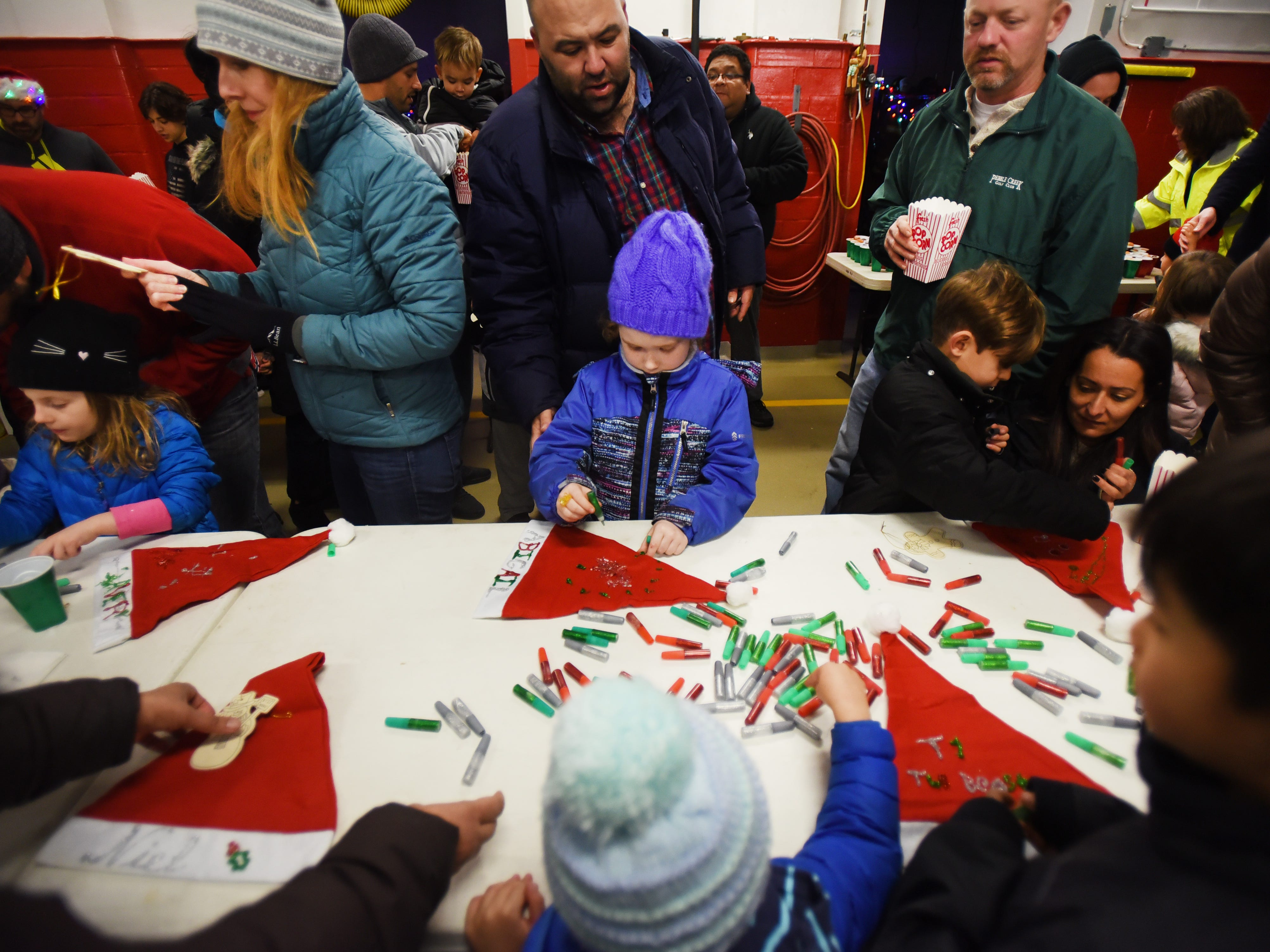 General scene of children and their parents working on decorating Christmas caps prior to the Christmas Tree Lighting ceremony at Cedar Grove Town Hall on 12/03/18.