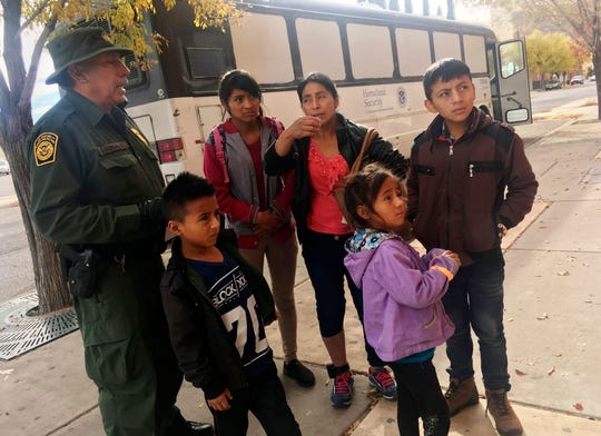 In this Thursday, Nov. 29, 2018 photo, a migrant family from Central America waits outside the Annunciation House shelter in El Paso, after a U.S. Immigration and Customs Enforcement officer drops them off. Volunteer shelters along the U.S.-Mexico border say they are preparing for an expected surge of new immigrants seeking asylum in the U.S. who will need temporary housing as the holidays approach.