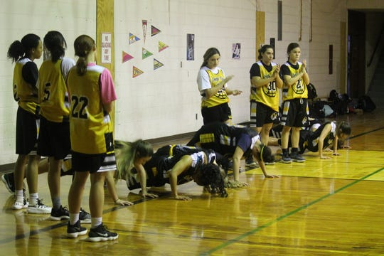 Members of the Alamogordo High School girls basketball teams do a quick set of push-ups during a recent practice.
