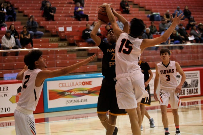 Navajo Prep's Treston Yazzie draws contact under the basket against Aztec's Austin Schaub (15) during the Jerry Richardson Memorial tournament Thursday at Shiprock. Prep is ranked ninth in the first 3A boys basketball poll of the season.