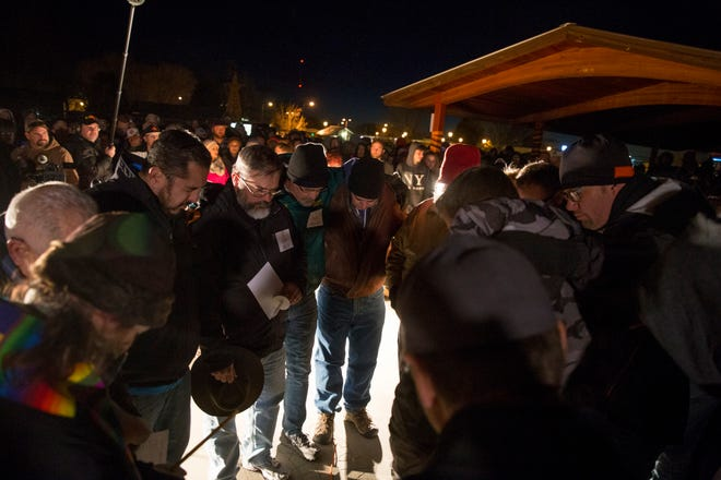 Local ministers and community leaders pray together before the start of a candlelight vigil on Dec. 7, 2017, at Minium Park in Aztec after the Aztec High School shooting.