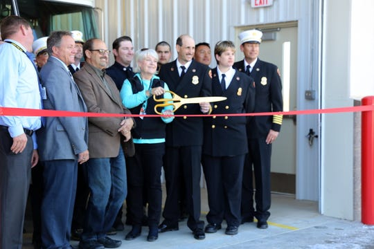 County officials and firefighters prepare to cut a red ribbon Tuesday during a ceremony at Lee Acres Fire Station No. 2.