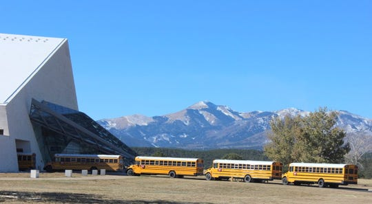 Buses line up to unload students at the Spencer Theater for Performing Arts with Sierra Blanca Peak looming in the background.
