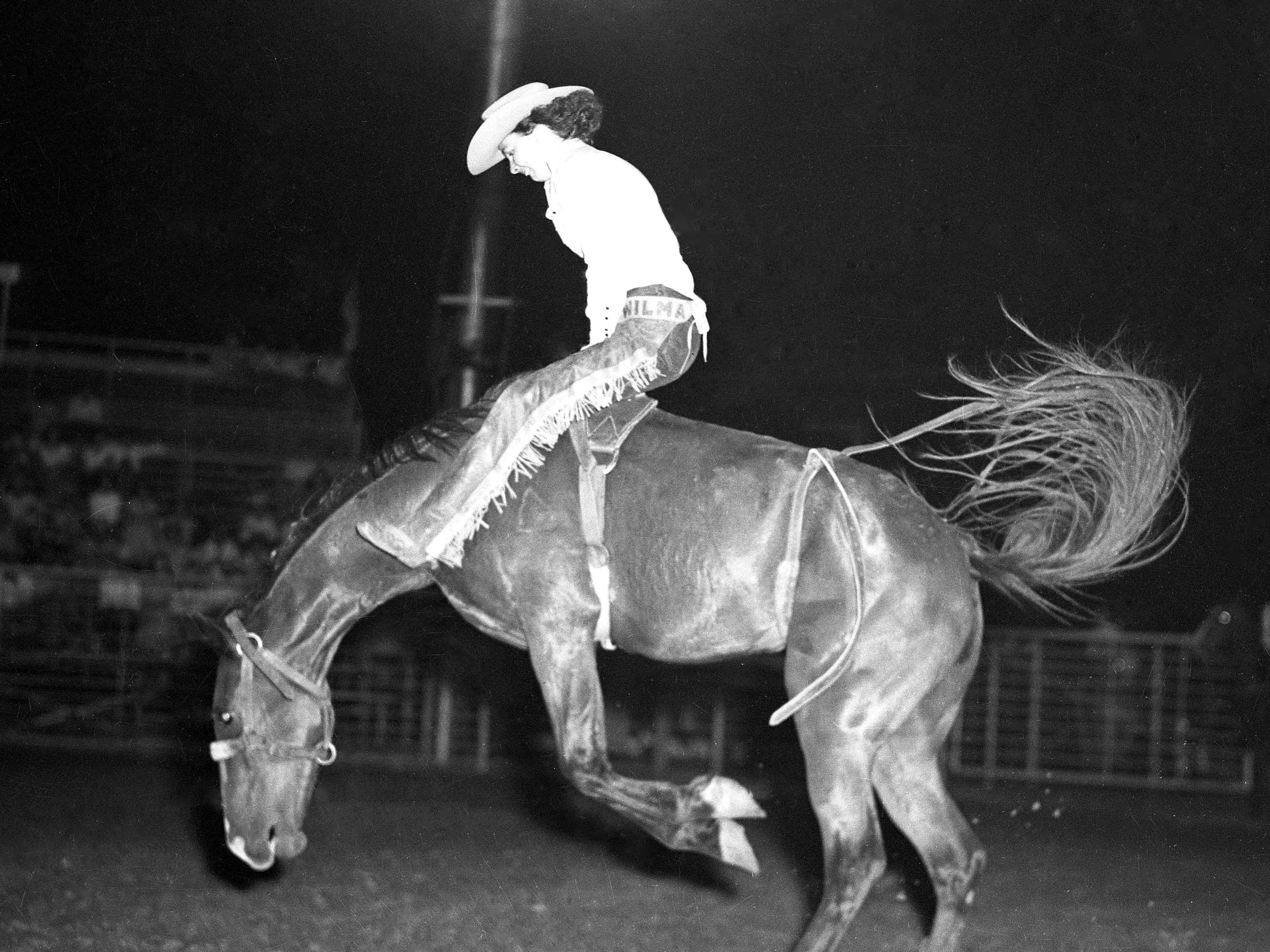 A cowgirl competes in a bronco busting competition during a 1940s Girls Rodeo Association sanctioned rodeo.