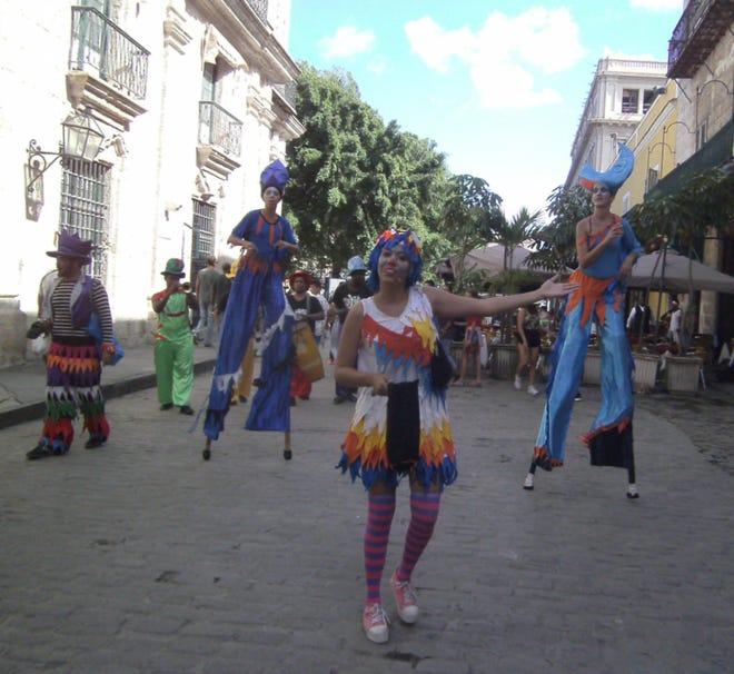 Colorfully costumed stilt walkers entertain Sunday strollers in Old Havana.