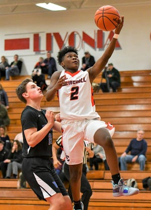 Churchill's Brandon Craddieth (2) goes in for the layup against Walled Lake Western.