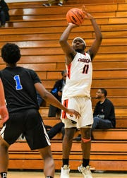 Churchill's Jaylen Stanley (11) launches the jumper in front of Western's Camron Williamson.